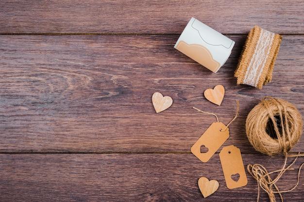 Свернутые кружева; деревянная форма сердца; метки и джутовая катушка на деревянном столе