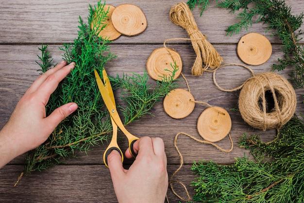 木製の机の上に手作りのホオジロを作るためのモミの小枝を切る人