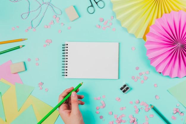 ティールの背景に緑色の鉛筆で空白のメモ帳に描く人のクローズアップ