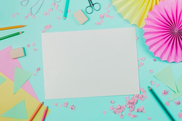 紙吹雪と白い空白の紙。色鉛筆;ターコイズブルーの背景にはさみと消しゴム
