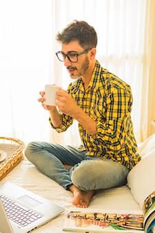 Мужчина сидит на кровати и пьет кофе, глядя на ноутбук
