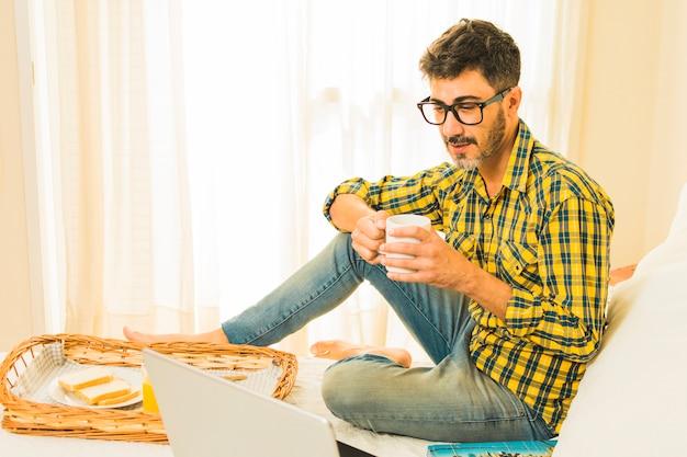 寝室でノートパソコンを見てベッドで朝食を持っている人