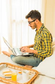 Вид сбоку человека, сидящего на кровати с подносом для завтрака с хлебом; сок и кофе