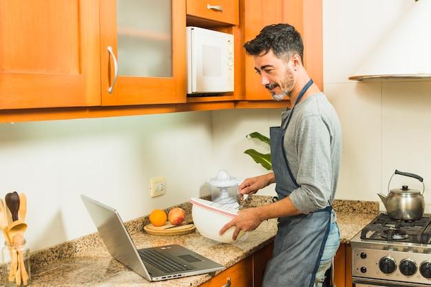男は台所でラップトップ上のレシピを見て食べ物を準備します。