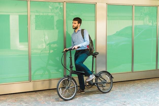 自転車の上に立って彼のバックパックを持つ男