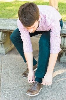 Мужчина сидит на скамейке в парке и завязывает шнурки