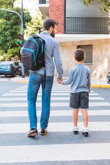 彼の息子と横断歩道を歩いてスクールバッグを運ぶ男の背面図