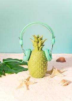 ビーチでヘッドフォンでプラスチック製パイナップル