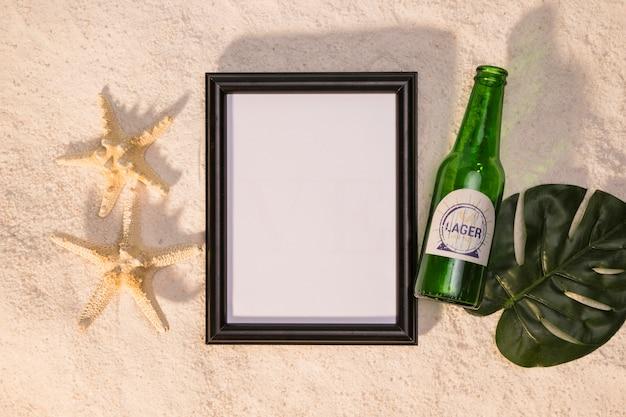 ホワイトボードのヒトデのボトルの飲み物と砂の上のモンステラの葉の組成