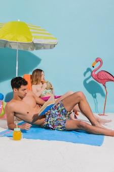砂とデッキチェアの上に横たわるとリラックスした水着の若いカップル