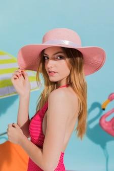 Молодая женщина в розовой шляпе и купальники позирует