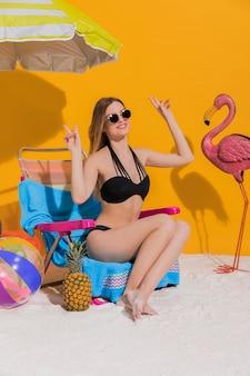 陽気な女性がビーチに座って