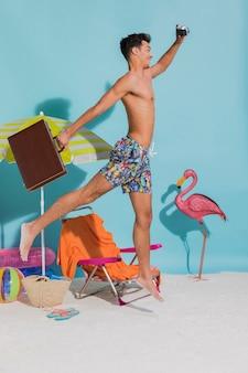 ビーチを走るスーツケースを持つ男