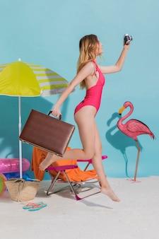 ビーチを走るスーツケースを持つ女性