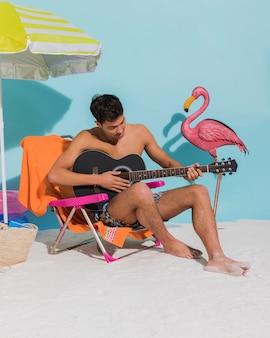 若い男がビーチでギターを弾く
