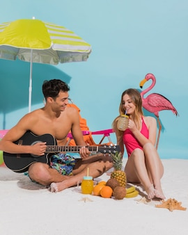 スタジオで砂の上に休んで若いカップル