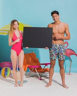 ビーチで空白の暗い看板を持って幸せな若いカップル