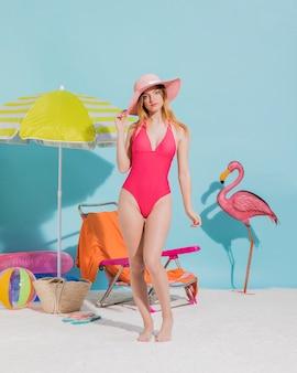 魅力的な若い女性がスタジオのビーチで帽子でポーズ