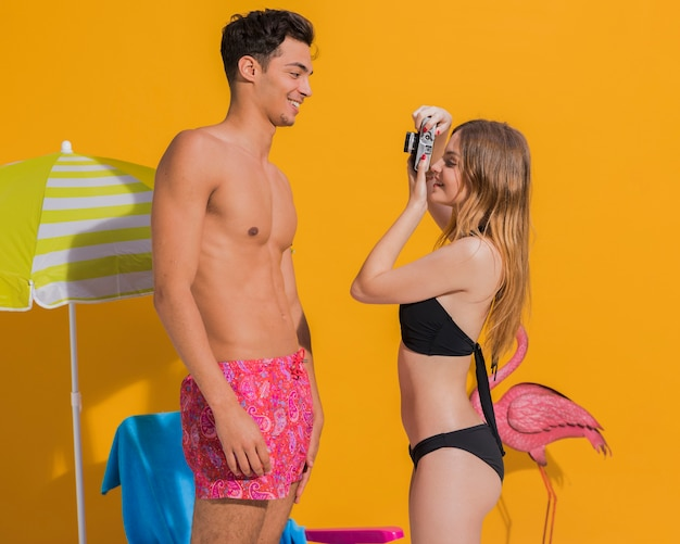 黄色の背景に陽気な若い男の写真を撮っているガールフレンド