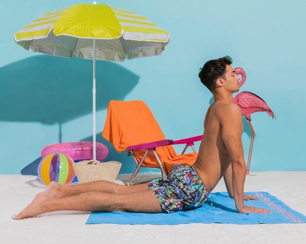 装飾的なビーチでヨガをやっている若い男