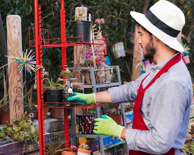 赤いラックに鉢植えの植物を配置する手袋を着用している人の側面図