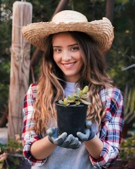 黒いサボテンの植物を保持している手袋を身に着けている笑顔の女性の肖像画