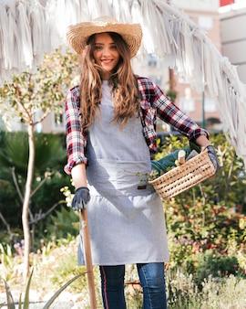 ツールとバスケットを庭で保持している笑顔の女性庭師の肖像画