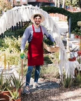 Портрет улыбающегося молодого мужчины садовник, проведение садовых инструментов и корзина