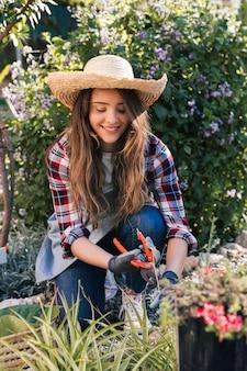 植物を剪定する女性庭師の肖像画を笑顔