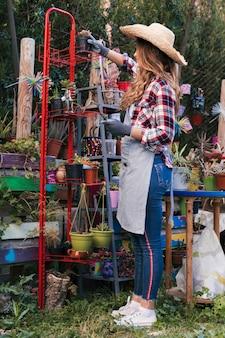 赤いラックに鉢植えの植物を配置する帽子をかぶっている女性庭師の側面図