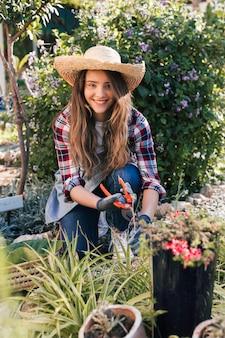 カメラを見て植物を剪定笑顔の若い女性の肖像画