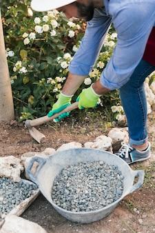 鍬で土を掘る男性庭師の俯瞰