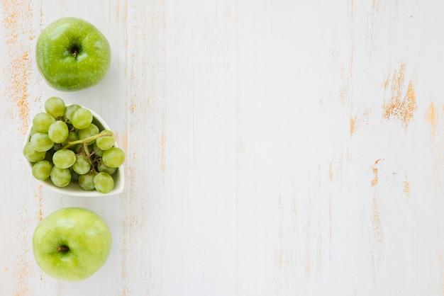 青リンゴと白い木製の背景上のブドウ