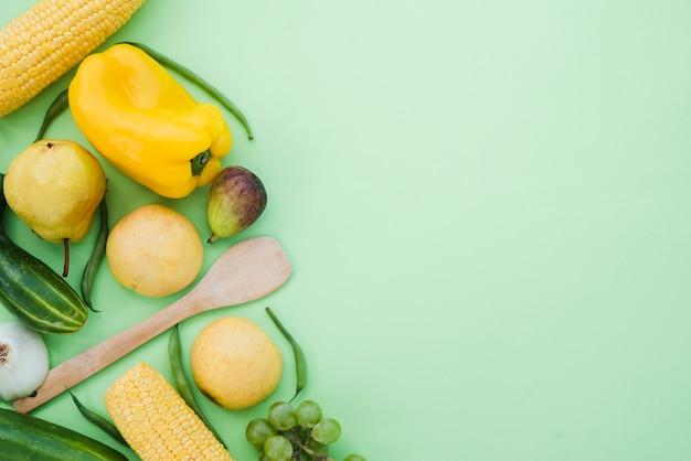 コーン;黄ピーマン。きゅうり;洋ナシ;イチジク;ぶどうとミントグリーンの背景に豆