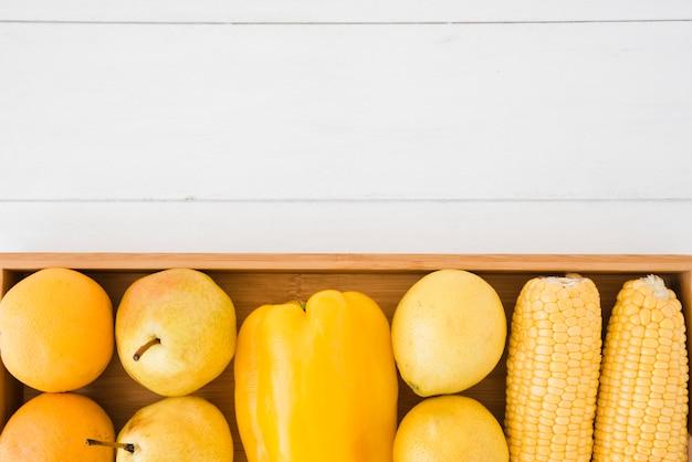 オレンジの俯瞰。洋ナシ;ピーマン;レモンとトウモロコシの白い机の上の木製トレイ