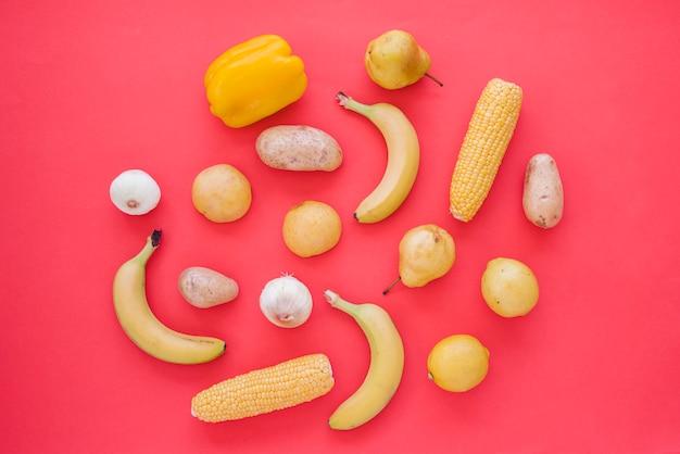 黄ピーマン。玉ねぎ;じゃがいも;洋ナシ;ライム;トウモロコシと赤の背景にニンニク
