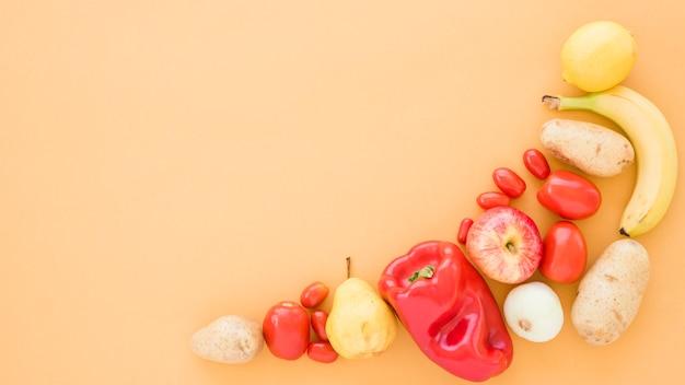 Томаты; картофель; груши; банан; яблоко и лайм на бежевом фоне