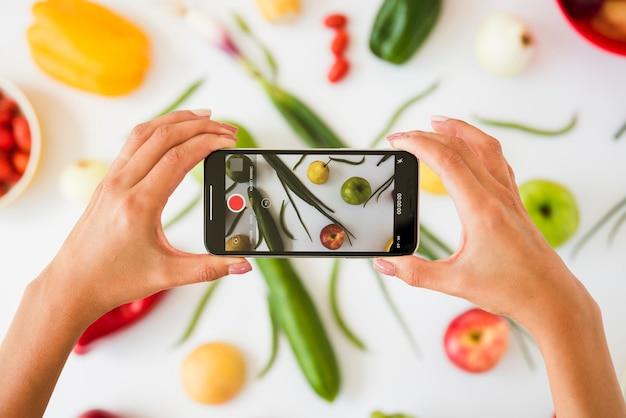 白い背景の上の野菜の写真を撮る人のクローズアップ