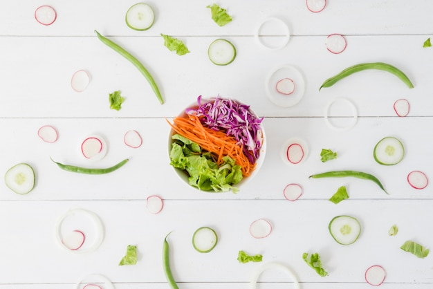 Тарелка салата с репой; огурец; ломтики лука с зеленой фасолью на деревянный стол