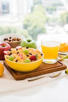 コーンフレークで健康的な朝食。ドライフルーツ;テーブルの上のリンゴとジュースのガラス