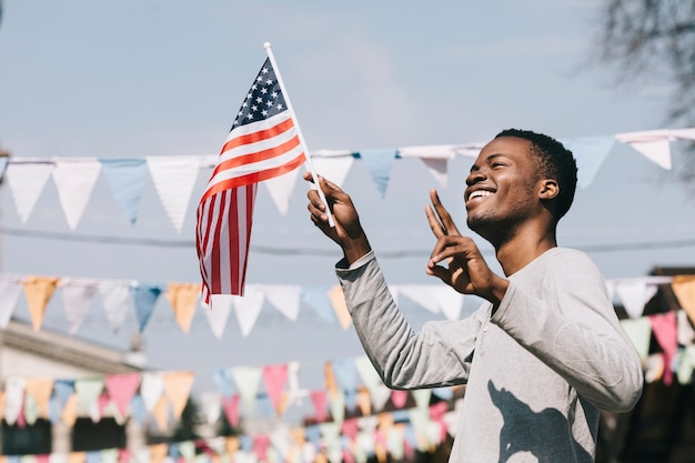 幸せなアフリカ系アメリカ人の男がアメリカの国旗を振って