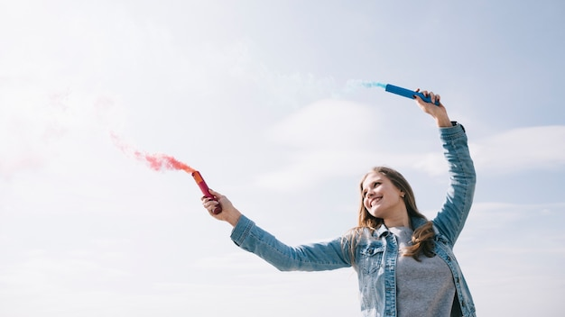 Жизнерадостная женщина, держащая дымовые факелы в вытянутых руках
