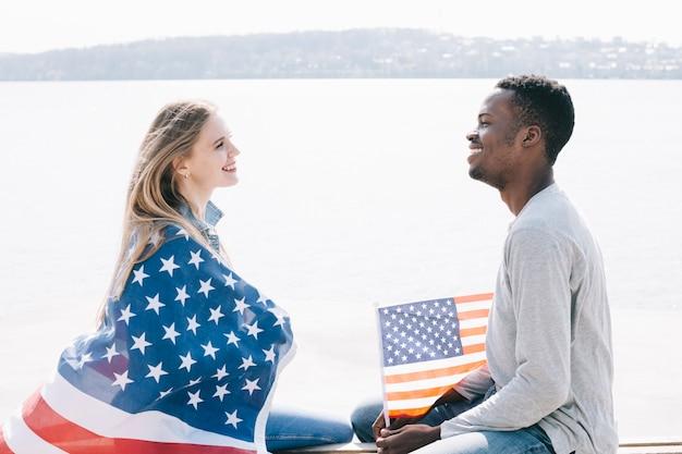 Молодые люди сидят на берегу моря и вместе улыбаясь держат американский флаг