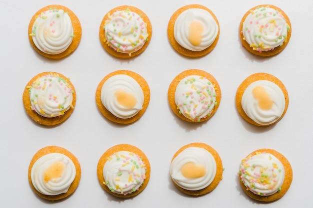 白い背景の上のホイップカップケーキの行