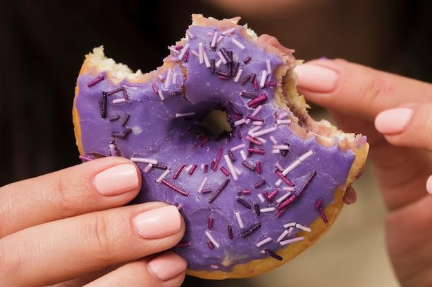 Крупный план женщины едят фиолетовый пончик