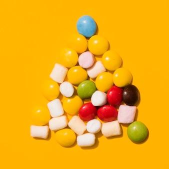 黄色の背景に白いマシュマロと三角形のキャンディー