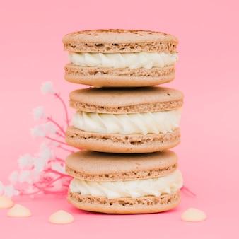 Сложены миндальное печенье с цветами на розовом фоне