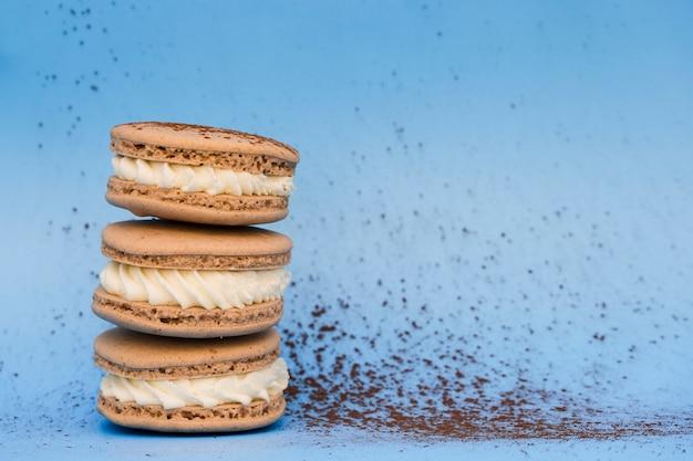 青い背景にホイップクリームと茶色のマカロン