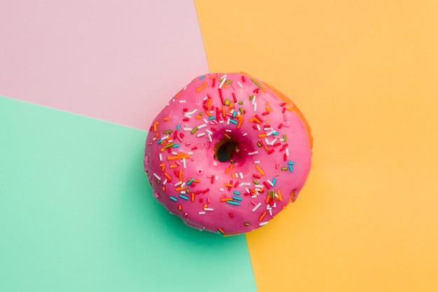 Розовый пончик на цветном фоне