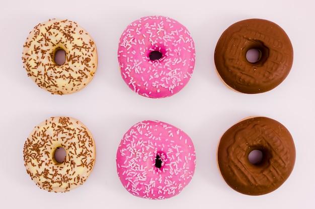 Бежевый; розовый и коричневый пончик на белом фоне